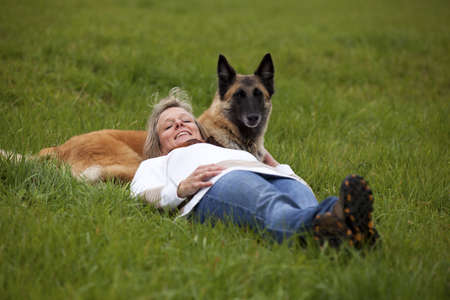 belgian: A smiling mature blond woman lying in the meadow and relaxing with her dog Stock Photo