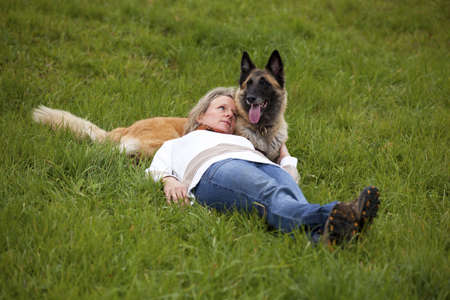 A mature blond woman lying in the meadow and relaxing with her dog photo