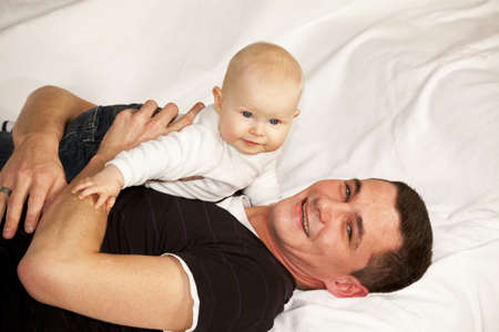 A happy and smiling father lying on a couch with his smiling baby girl photo