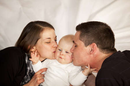 A young mother and a young father kissing their baby girl on her cheeks