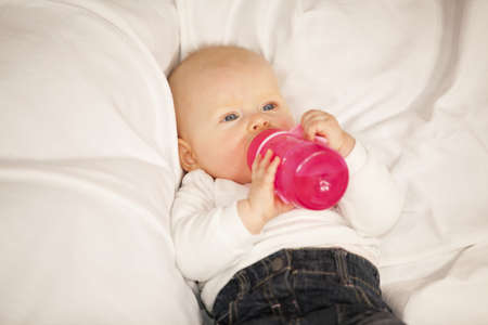 A relaxed eight months old baby girl lying on a couch and drinking from her baby bottle