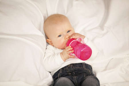 A relaxed eight months old baby girl lying on a couch and drinking from her baby bottle photo