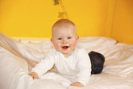 A happy and laughing eight months old baby girl lying on a changing table photo
