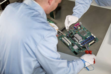 IT - engineers doing repairs and cleaning on a motherboard