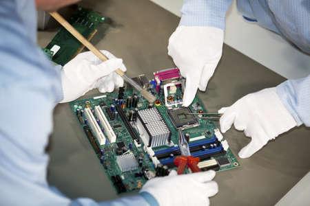 componentes: SE - ingenieros haciendo reparaciones y limpieza en una placa base en el z�calo del procesador Foto de archivo