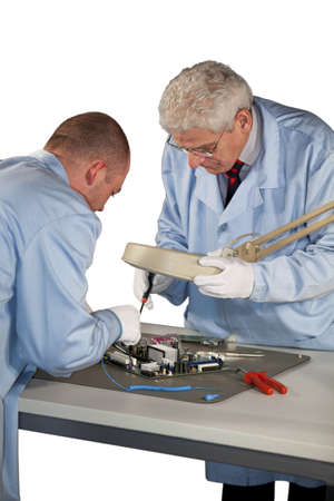 IT - engineers doing repairs on a motherboard photo