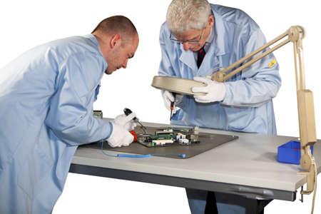 IT - Ingenieure, die Reparaturen auf einem Motherboard zu tun Standard-Bild