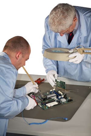 IT - engineers doing repairs on a motherboard and plugging in a graphic card photo