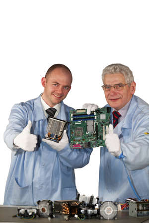 repairing: �xito-ingenieros de presentar una motherboard, un ventilador y posando con los pulgares arriba signo Foto de archivo