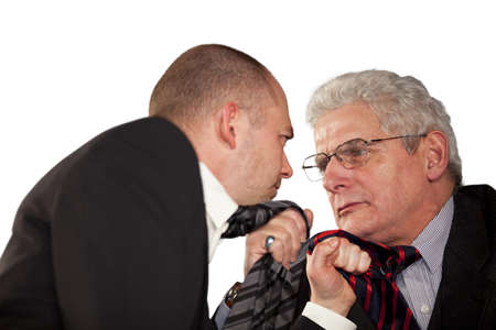 Two angry businessmen standing face to face and tearing each others tie