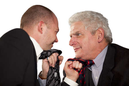Two angry businessmen standing face to face and tearing each others tie photo