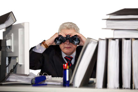 A senior businessman sitting behind his desk looking through binoculars