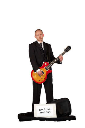 An unemployed man in a business dress playing guitar for money photo