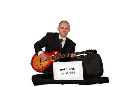 sacked: An unemployed man in a business dress playing guitar for money Stock Photo