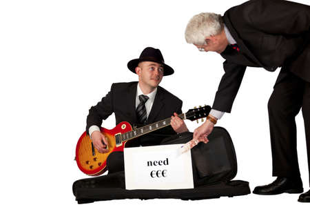 solicit: An unemployed man in a business dress playing guitar for money Stock Photo