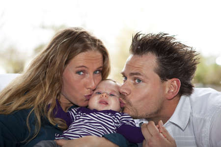 A proud young mother and father kissing their eight weeks old baby girl on her cheeks photo
