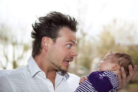 joking: A happy father making faces and joking with his eight weeks old baby girl Stock Photo