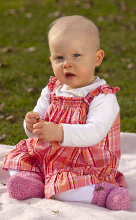 A one year old baby girl sitting on a blanket in the meadow photo