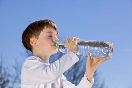 surprised child: a 9 years old boy drinking water from a bottle