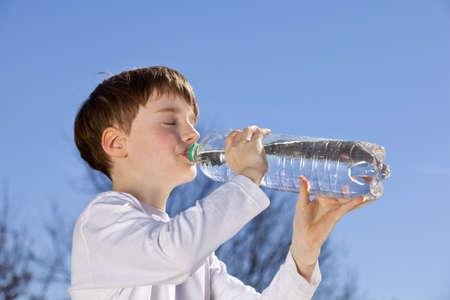 ein 9 Jahre alt Boy Trinkwasser aus einer Flasche Standard-Bild