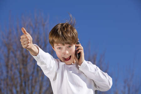 A laughing 9 years old boy with a cell phone posing thumbs up