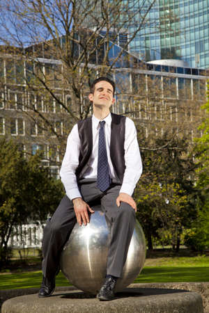 A smiling businessman sitting on a huge steel ball in a park and relaxing during his lunch break and enjoying the sun photo