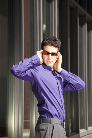 A male fashion model with sunglasses posing in the sunlight photo