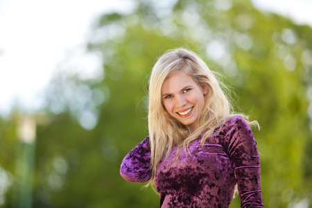 A smiling beautiful blond fashion model with a tree in the background Stock Photo - 9584845