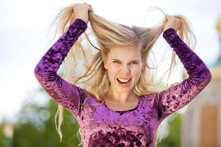 An angry beautiful blond fashion model tearing her hair photo
