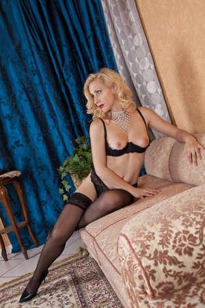 Egy szexi fehérnemű modell pózol a kanapén, fényképezett egy kék függöny a háttérben