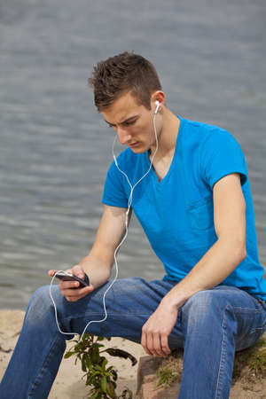 A thoughtful young man with a smartphone listening to music and sitting next to a river photo