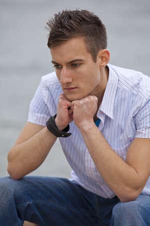 Eine nachdenkliche modische junge Mann sitzt neben einem Fluss
