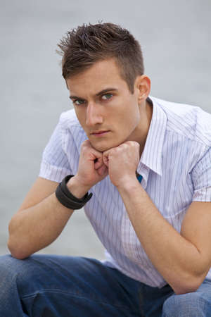 A serious looking fashionable young man sitting next to a river photo