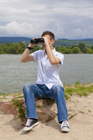 A young man with binoculars sitting next to a river and looking at something photo