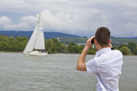 A young man with binoculars standing next to a river and looking at a sailing yacht photo