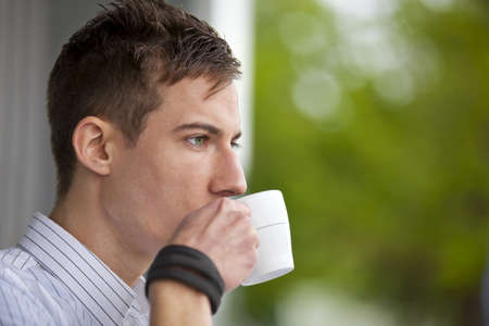 Vértes egy fiatal férfi iszik valamit egy csésze Stock fotó