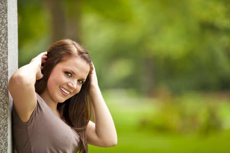 area sexy: A smiling beautiful brunette woman in her twenties standing outside a building  in a park