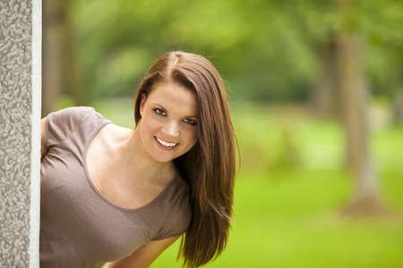 busty: Een lachende mooie brunette vrouw twintiger permanent buiten een gebouw in een park