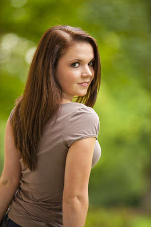 area sexy: A cool looking beautiful brunette woman in her twenties standing in a park and looking into the camera