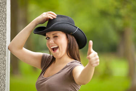 area sexy: A laughing beautiful brunette woman with a cowboy hat in her twenties standing outside a building in a park and posing with the thumbs up sign