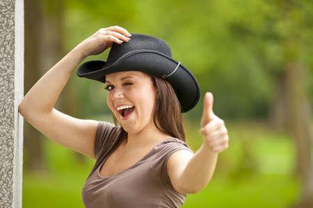 clin d oeil: Une belle femme brune en riant avec un chapeau de cow-boy dans la vingtaine debout � l'ext�rieur d'un b�timent dans un parc et posant avec le pouce lev� signe