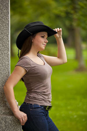 area sexy: A thoughtful beautiful brunette woman with a cowboy hat in her twenties standing outside a building in a park and looking at something