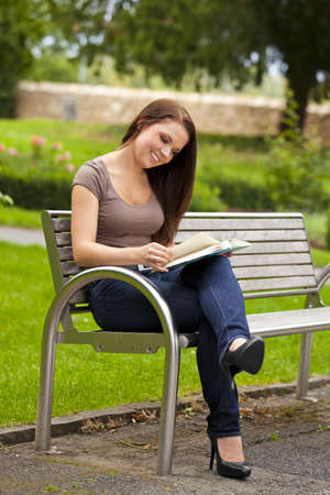 A smiling beautiful brunette woman in her twenties sitting on a bench in a park and reading a book Stock Photo