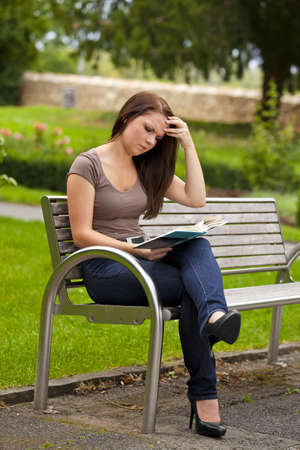a concentrated beautiful brunette woman in her twenties sitting on a bench in a park and reading a book photo