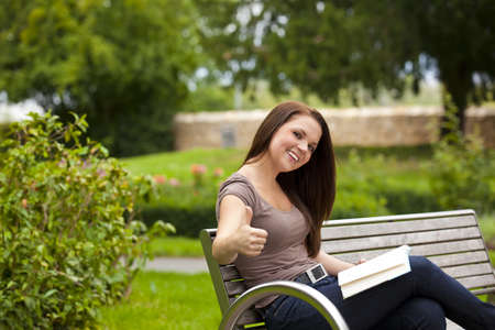 A laughing beautiful brunette woman in her twenties sitting on a bench in a park with a book and posing with the thumbs up sign photo