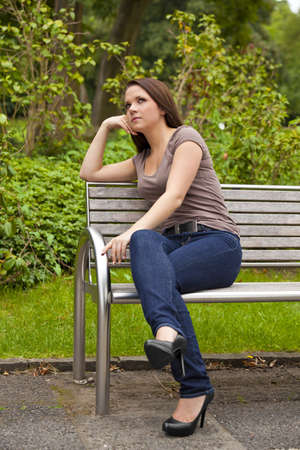 area sexy: A thoughtful beautiful brunette woman in her twenties sitting on a bench in a park and looking at something