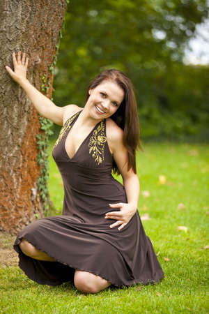 eyes looking down: A smiling beautiful brunette woman in her twenties posing in a park next to a tree