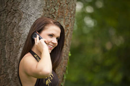 A smiling beautiful brunette woman in her twenties with a cell phone standing in a park in front of a tree Stock Photo - 10684544