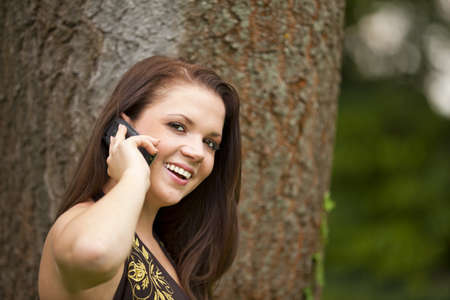 A smiling beautiful brunette woman in her twenties with a cell phone standing in a park in front of a tree photo