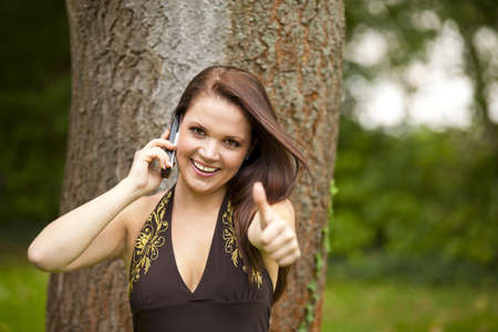 area sexy: A smiling beautiful brunette woman in her twenties with a cell phone standing in a park in front of a tree and posing with the thumbs up sign